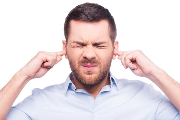 C'est trop fort ! homme mûr frustré en chemise tenant les doigts dans ses oreilles et gardant les yeux fermés en se tenant debout sur fond blanc