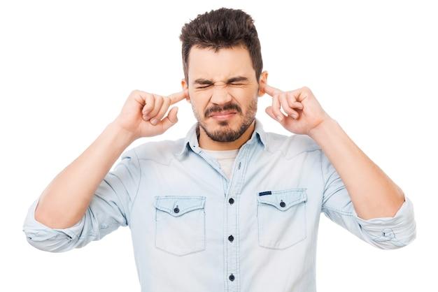 C'est trop fort ! jeune homme frustré en chemise tenant les doigts dans ses oreilles et gardant les yeux fermés en se tenant debout sur fond blanc