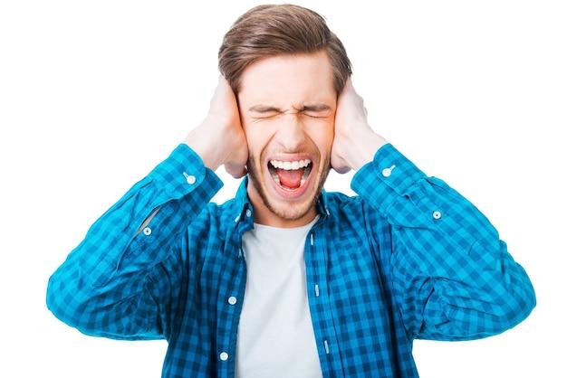 C'est trop fort ! jeune homme frustré tenant la tête dans les mains et gardant les yeux fermés