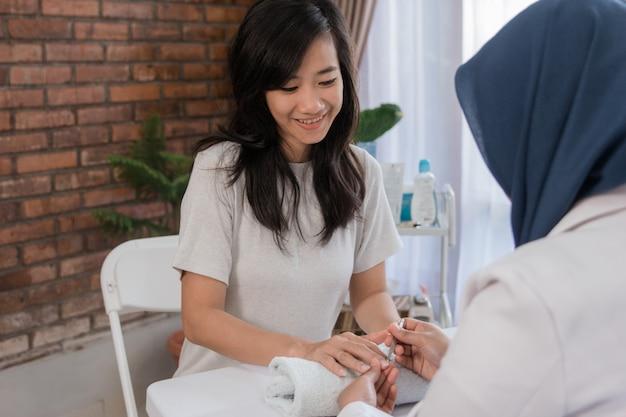Esthéticienne à l'aide d'un poussoir à cuticules offrant un service client