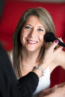 Esthéticienne appliquant le fard à joues à une joyeuse jeune femme avec un sourire heureux à l'aide d'une grande brosse à cosmétiques doux