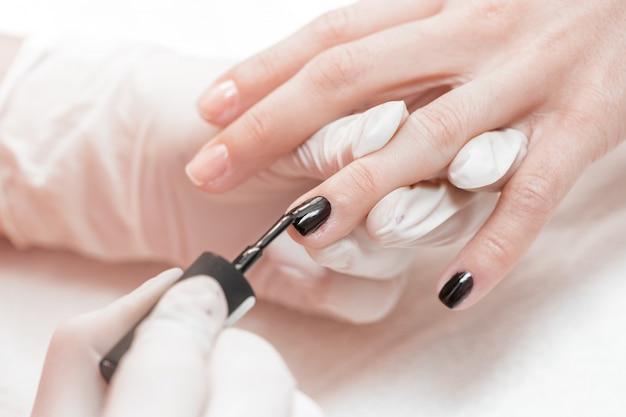 Esthéticienne appliquant des ongles polonais aux ongles des femmes