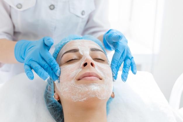 Une esthéticienne applique un masque sur le visage d'un patient pour les soins de la peau