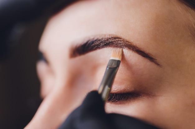 Esthéticienne applique de la peinture au henné sur les sourcils taillés dans un salon de beauté