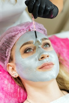Esthéticienne, appliquer le masque à la femme en clinique