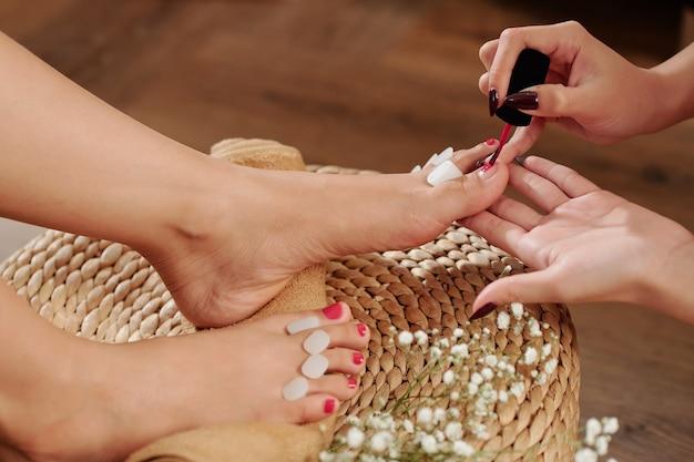 Esthéticienne, appliquer le vernis à ongles rouge