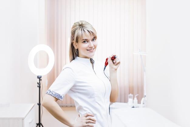 Esthéticienne belle femme avec un sourire sur votre visage dans la beauté du cabinet avec l'outil pour le maquillage permanent en rukakh