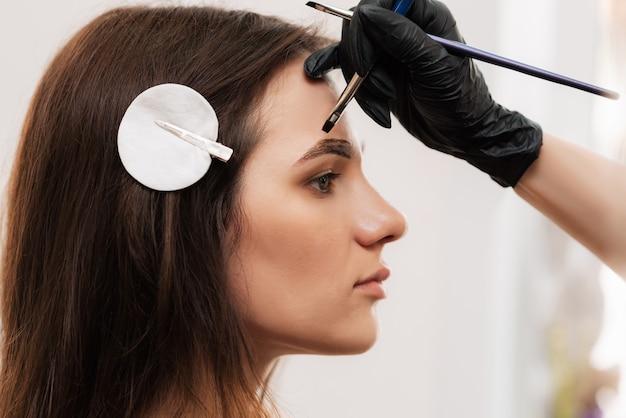 L'esthéticienne-broviste donne forme en appliquant du henné au pinceau, en colorant les sourcils en institut de beauté. soins du visage professionnels