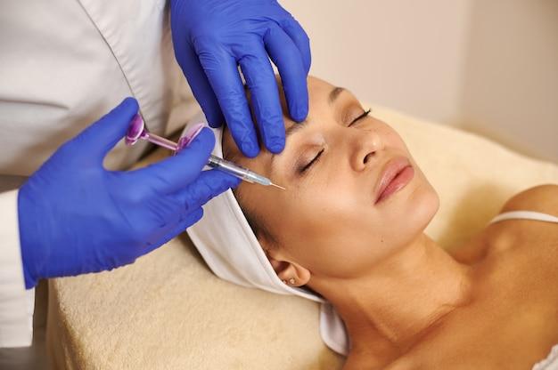 Esthéticienne cosmétologue fait des injections de beauté dans le visage de la belle femme
