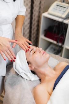 Esthéticienne dans un salon de beauté spa applique la crème sur le visage d'un client, une fille se trouve sur une table de cosmétologie