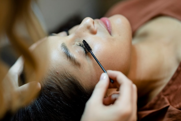 Esthéticienne donnant un traitement des cils à un client dans un salon de beauté