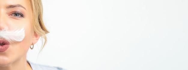 Esthéticienne drôle avec une moustache en forme de plume blanche pose sur fond blanc, concept d'épilation.