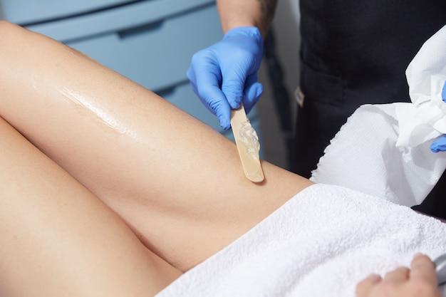 Esthéticienne enlevant les cheveux de la jambe de la jeune femme avec laser