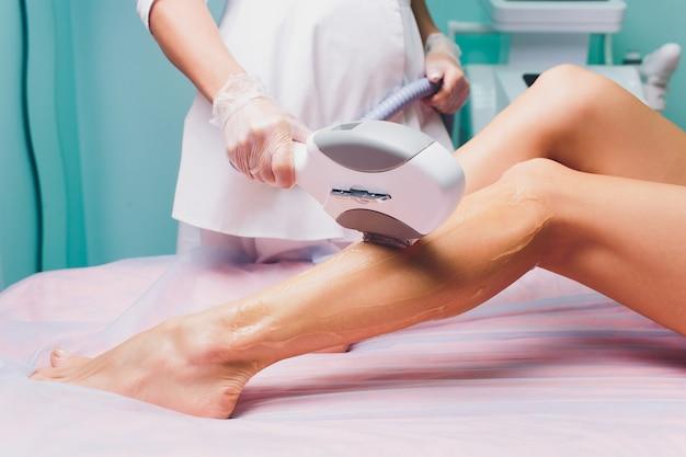 L'esthéticienne enlève les cheveux sur de belles jambes féminines à l'aide d'un laser. épilation sur les jambes, procédure au laser à la clinique.