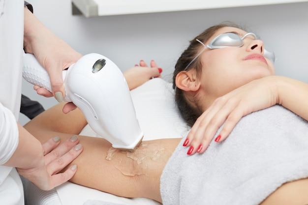 Esthéticienne enlever les cheveux de jeune femme au laser