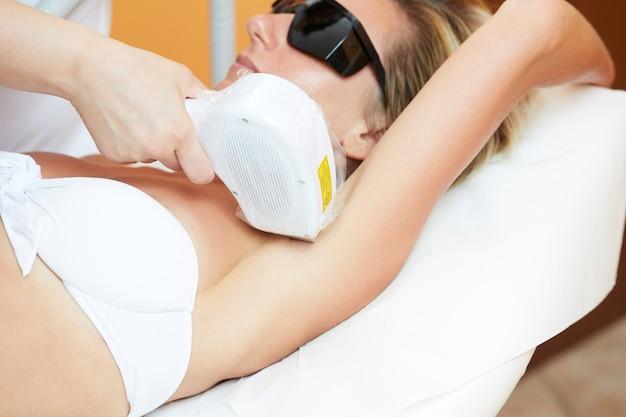 Esthéticienne épilant une jeune femme au laser
