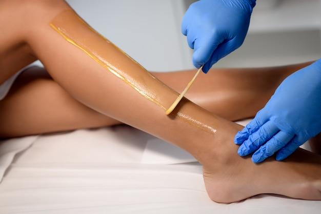 Esthéticienne, épilation des jambes féminines au centre de spa