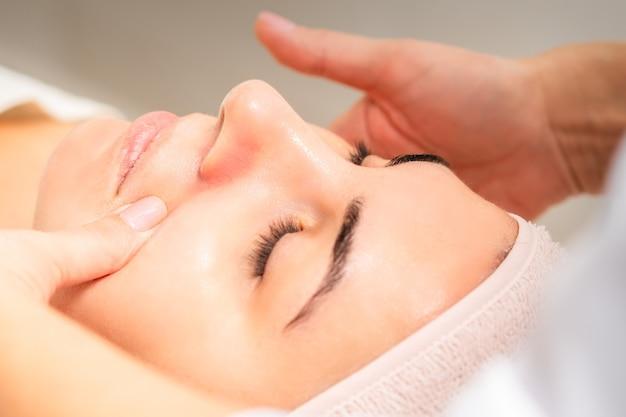 Esthéticienne faisant un massage du visage par drainage lymphatique ou un massage lifting au salon de beauté.
