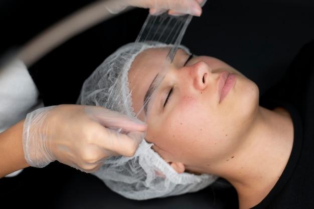 Esthéticienne faisant une procédure de microblading sur une femme dans un salon de beauté