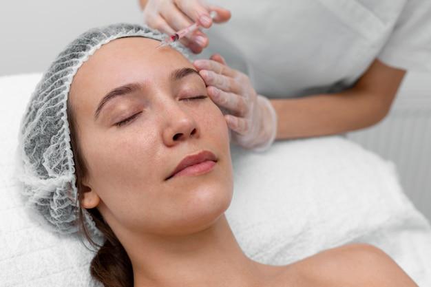 Esthéticienne faisant remplissage d'injection sur une cliente