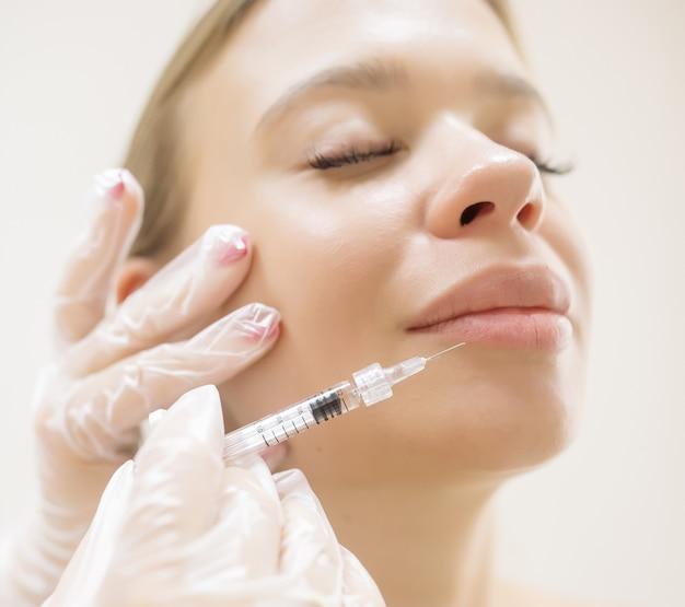 L'esthéticienne fait l'augmentation patiente des lèvres à l'aide d'injections de la charge d'acide hyaluronique