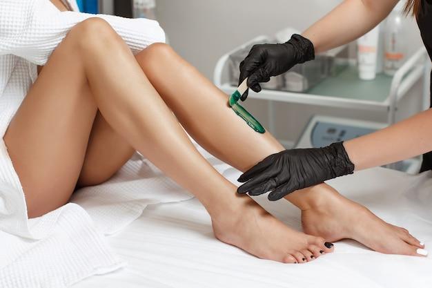 Esthéticienne fait l'épilation de la jeune femme sur sa jambe avec de la cire