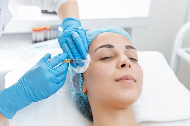 Esthéticienne fait des injections de beauté dans la peau d'une belle jeune femme