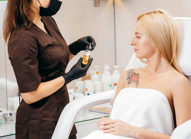 Esthéticienne féminine effectue la correction des sourcils sur de beaux modèles en cabine cosmétique