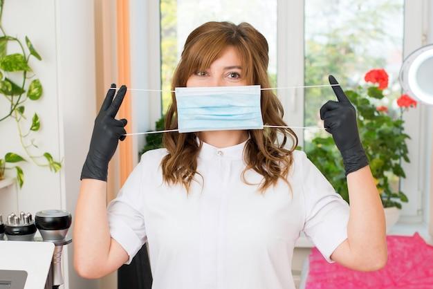 Esthéticienne femme mettant un masque de protection bleu à la clinique de beauté