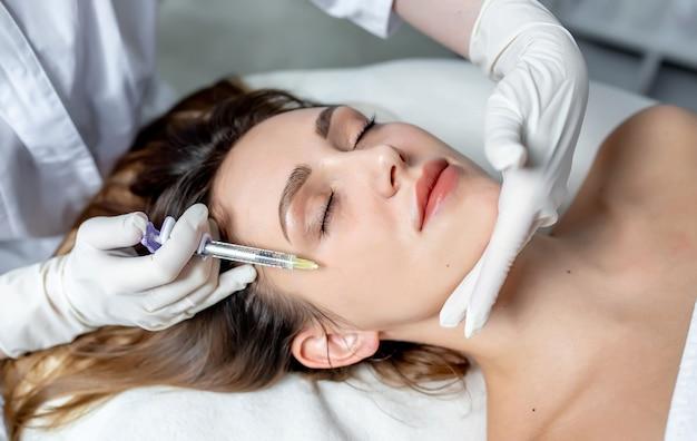 Esthéticienne fille fait des injections sur les lèvres et le visage d'une belle femme dans un coin cosmétique