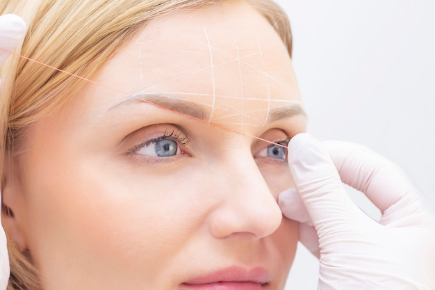 Esthéticienne de fille marque à l'aide du tatouage de sourcil de fil. maquillage permanent. tatouage permanent des sourcils.