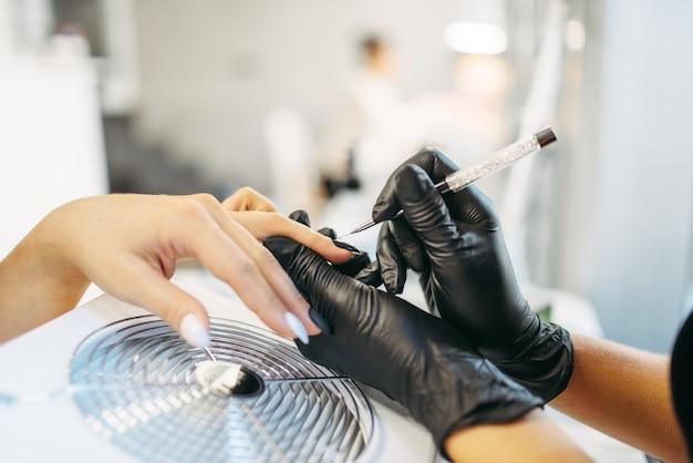 Esthéticienne en gants noirs colle les ongles du client, manucure en salon.