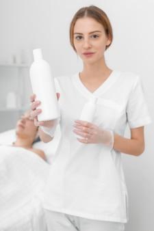 Esthéticienne avec lotion pour cliente