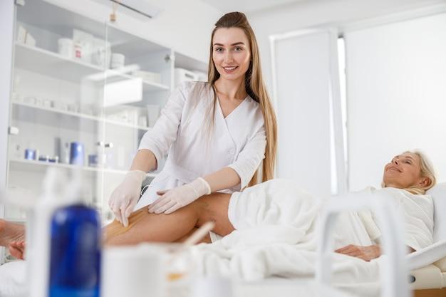 Une esthéticienne a mis de la cire dépilatoire sur la jambe de la femme âgée pour l'épilation.