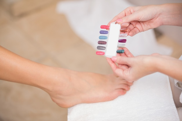 Esthéticienne montrant les couleurs des ongles du client