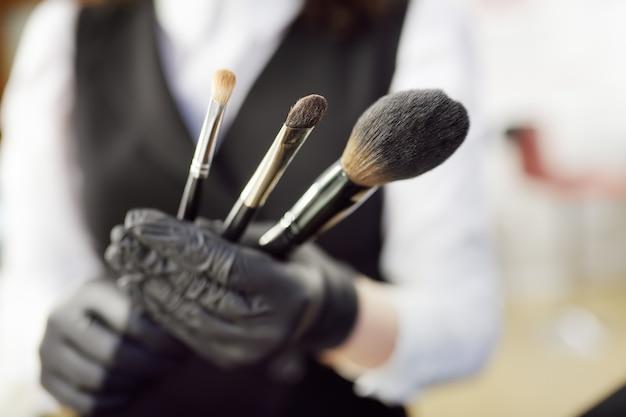 Esthéticienne montre des pinceaux pour le maquillage et prépare leur utilisation.