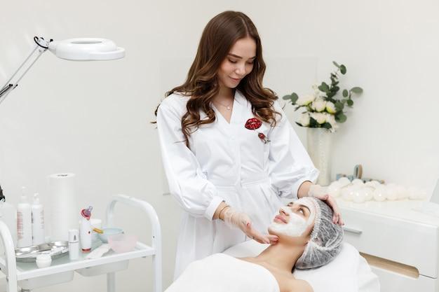 Esthéticienne avec patient dans un masque sur son visage au bureau