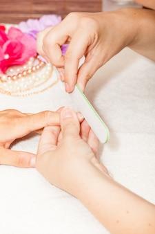 L'esthéticienne polit les ongles du client avant de mettre du vernis à ongles