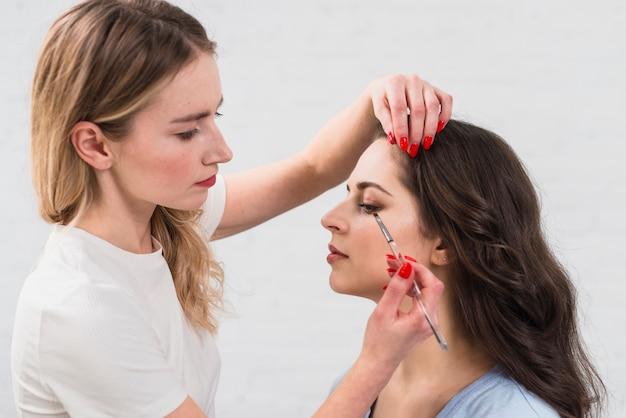 Esthéticienne se maquiller pour une jeune femme
