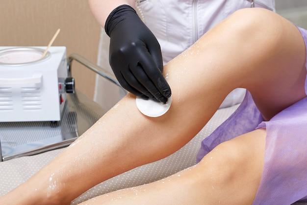 Esthéticienne se prépare à épiler les jambes féminines dans le centre de spa. préparation à l'épilation