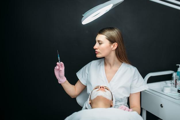Esthéticienne avec seringue dans les mains, injection de botox