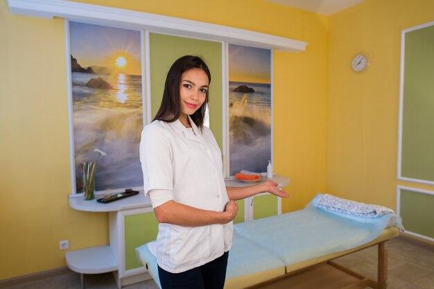 Esthéticienne souriante debout à côté de la table de massage au spa et accueille les clients invite