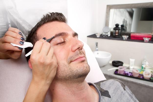 Esthéticienne en train de cueillir un homme beau les sourcils avec une pincette dans un salon de beauté