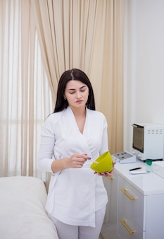Esthéticienne en uniforme blanc mélange le masque dans un bol vert au bureau