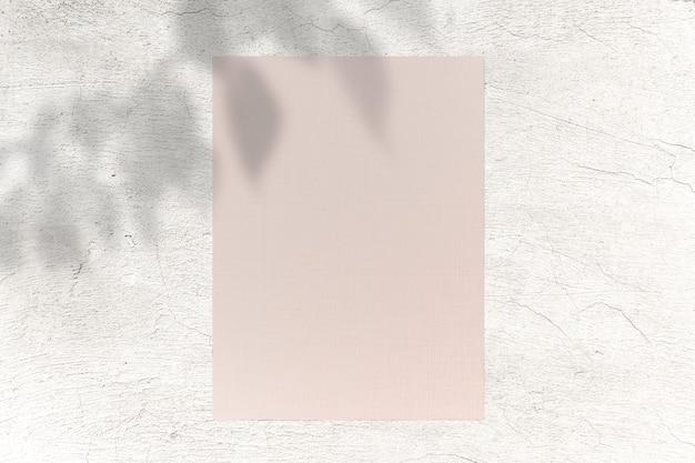 Estompée de l'ombre de la branche et du papier vide sur la texture du béton.