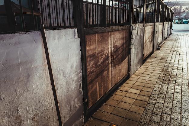 Étable vide avec portes en bois sales dans une ferme.