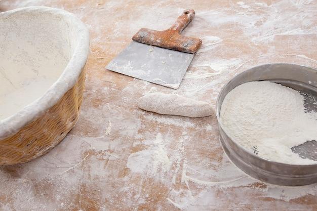 Établi de boulangerie avec spatule, panier de farine, tamis et pain formaté