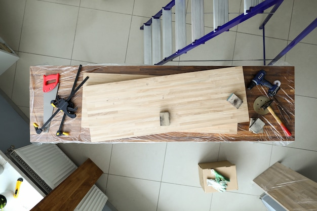 Sur l'établi se trouvent des feuilles et des outils plaqués en bois