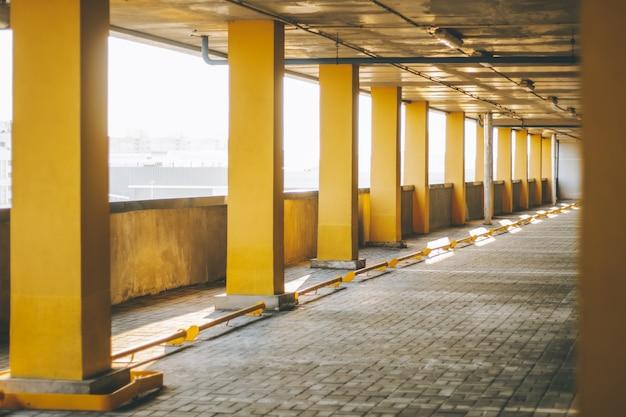 Étage d'un parking hors sol à plusieurs niveaux, avec des rangées de colonnes jaunes
