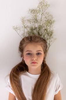 Étage. petite dame réfléchie tranquille allongée sur un bouquet de fleurs tout en ayant les cheveux attachés en queue